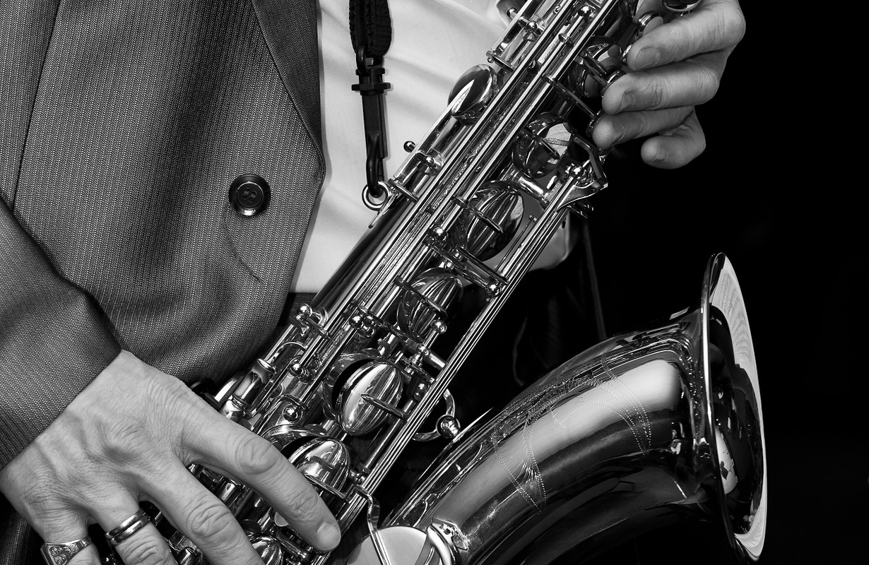The man playing the saxophone in black and white