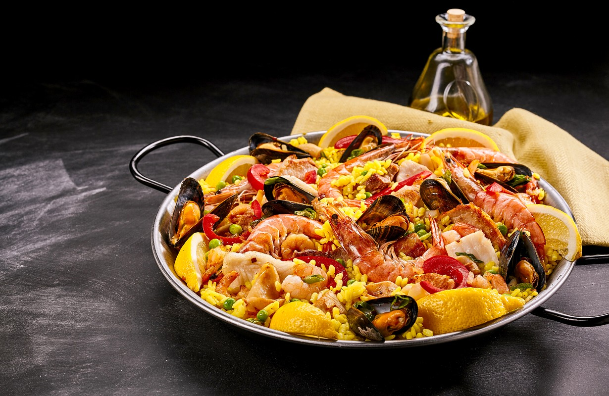 Close Up of Colorful Spanish Seafood Paella Rice Dish with Fresh Shellfish Served with Lemon Wedges in Pan on Smudged Chalkboard Background with Oil and Napkin