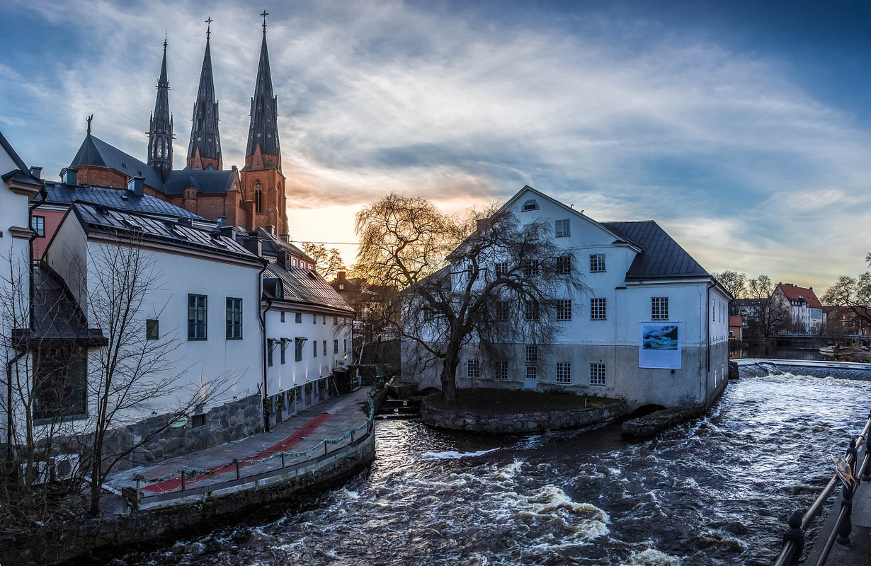 View of the cathedral, the river Fyris and the Uppland museum at sunset in Uppsala, Sweden