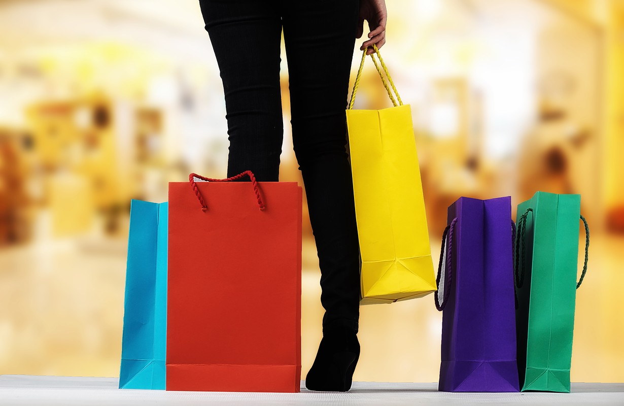 Young woman with shopping bags over shopping mall background with copy space. Shopping concept.