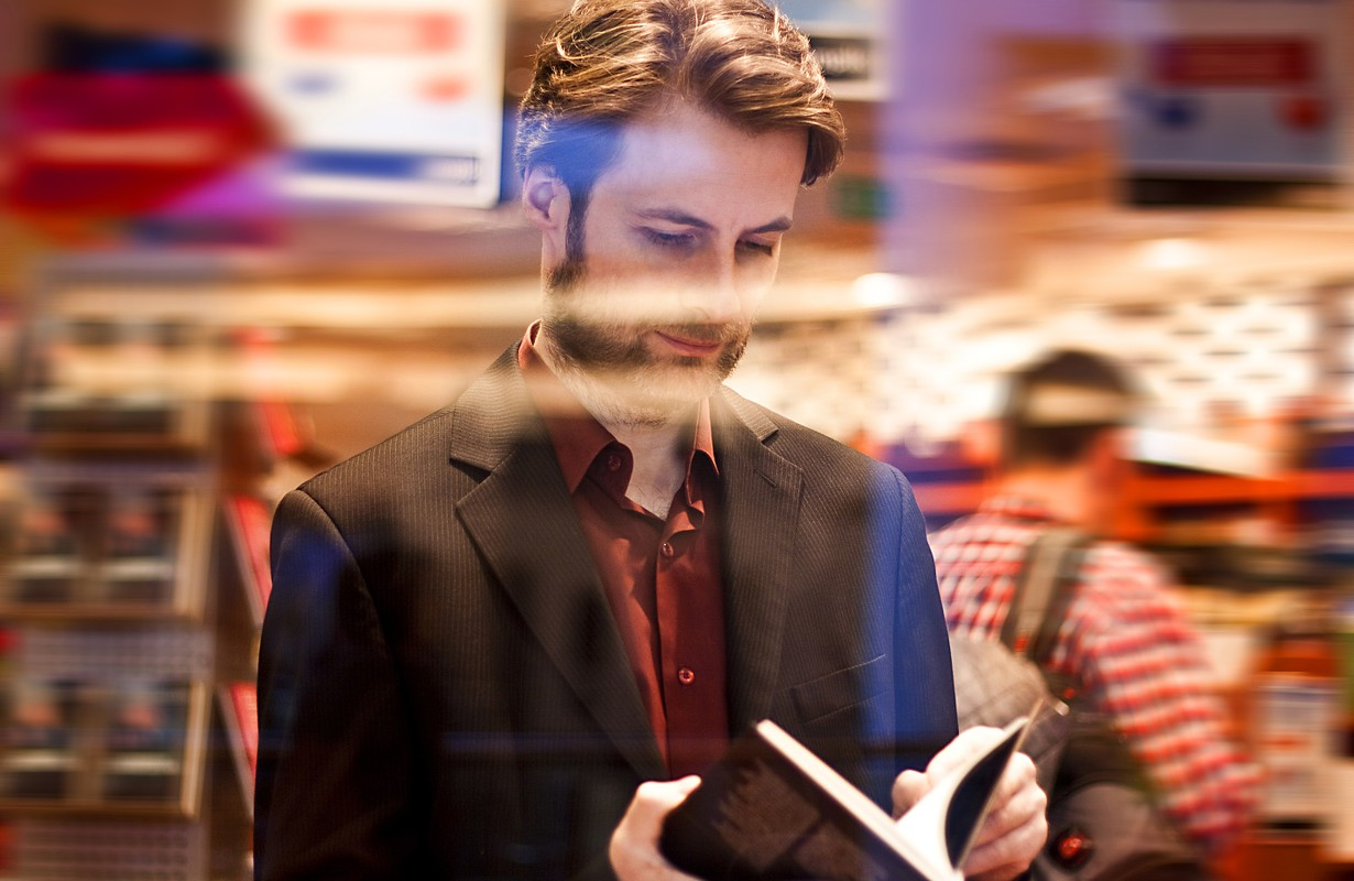 Forty years old elegant man standing inside bookstore reading a book