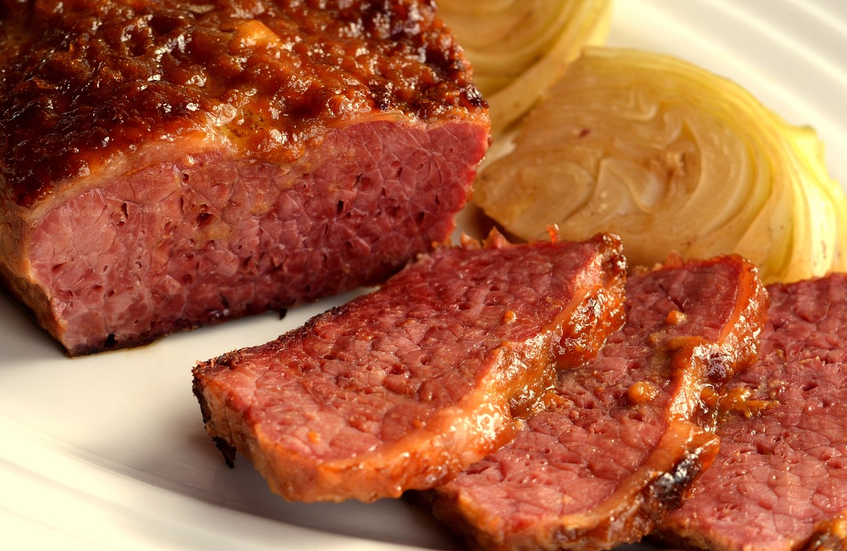 Corned Beef and Cabbage: Traditional Irish Cuisine. Braised and then glazed corned beef served on a white plate with cabbage wedges