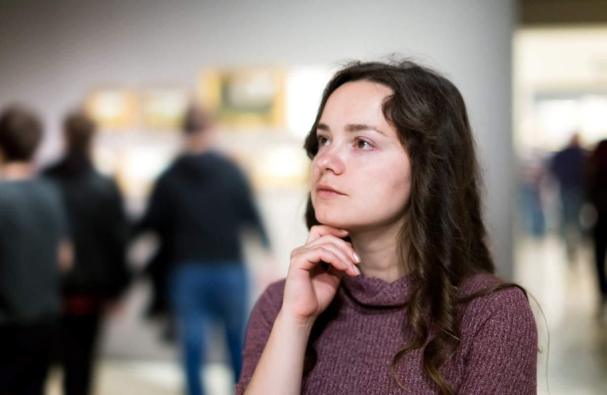 Portrait of attractive young woman attentively looking at paintings in art museum