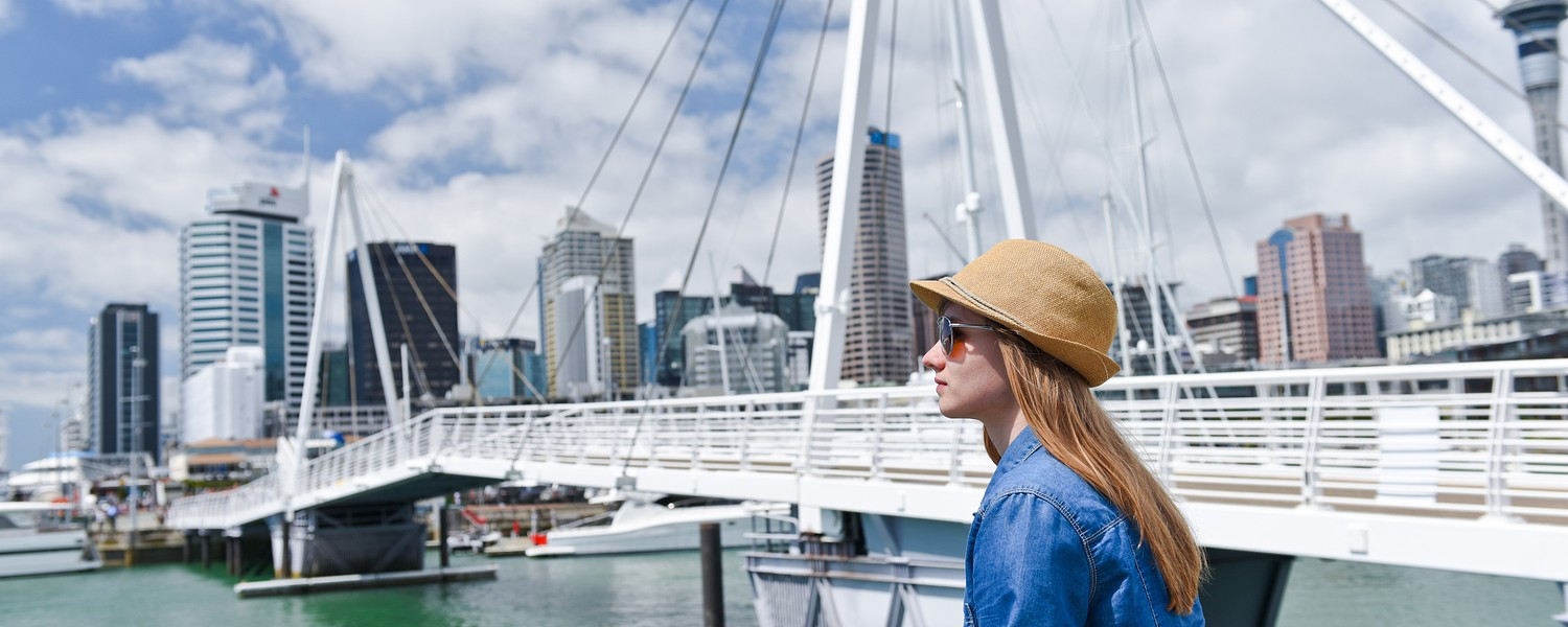 Young traveler woman in hat looking at opening Bridge in Auckland, New Zealand. City life