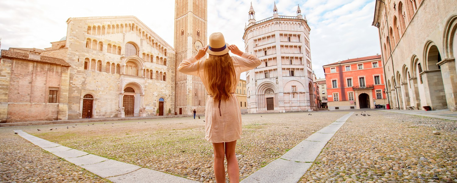Young female tourist standing back on the central square with cathedral and famous leaning tower on the background in Parma town. Having great vacations in Parma
