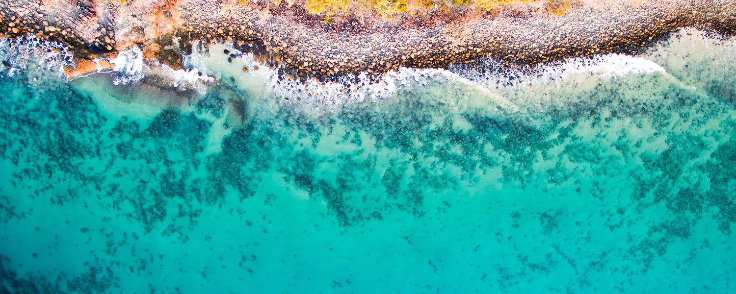 birds-eye view of a rocky beach and clear azure ocean water