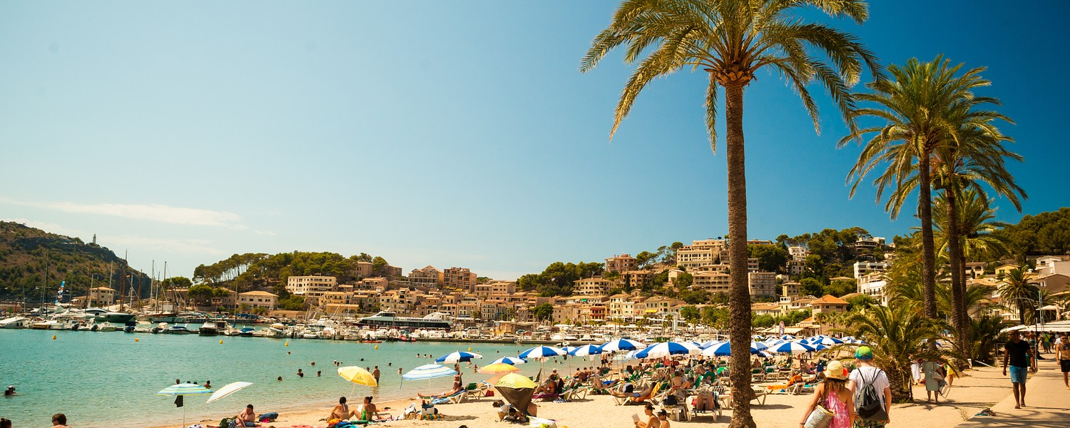 View of the beach of Port de Soller with people lying on sand and the old buildings visible in background, Soller, Balearic islands, Spain.