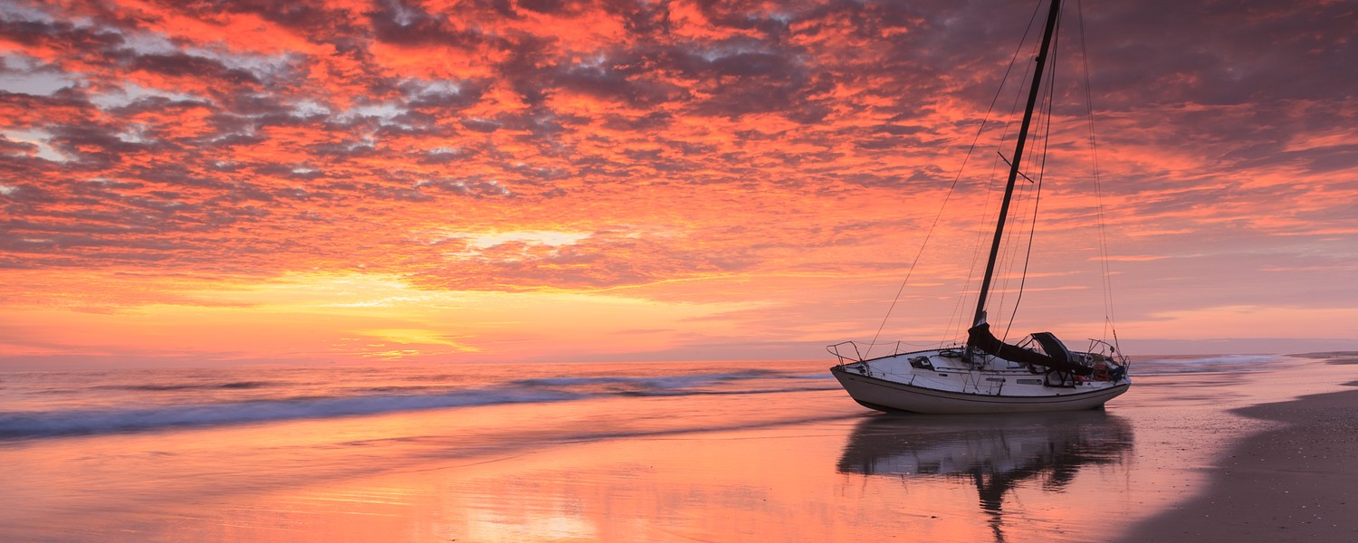 Landscape of sunrise and beached boat on coast of the Atlantic Ocean in the Outer Banks of North Carolina
