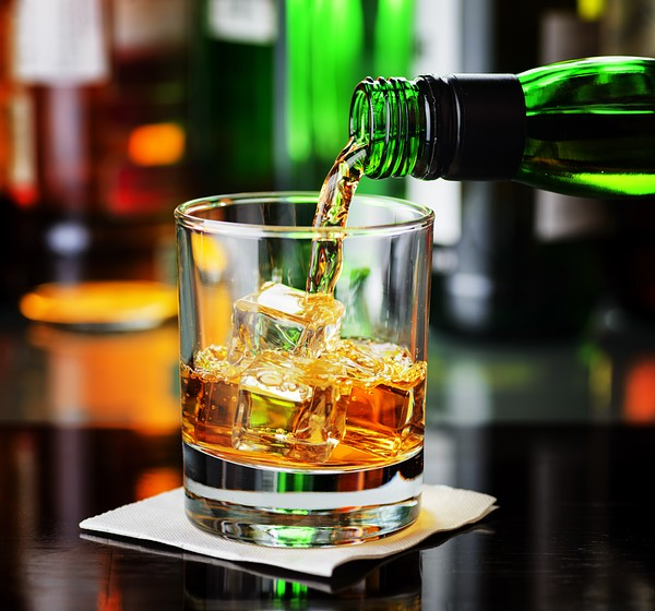 Whiskey pouring from a bottle into a glass in a bar. Scotch and Irish Single Malt or Blended Whiskey.