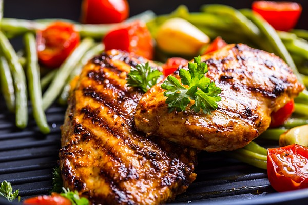 Grilled chicken breast in different variations with cherry tomatoes, green French beans, garlic, herbs, cut lemon on a wooden board or teflon pan. Traditional cuisine. Grill kitchen.