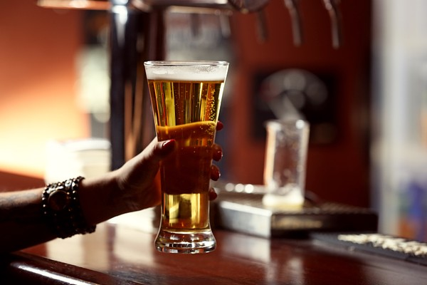 Woman holding beer glass, close-up, on bar interior background